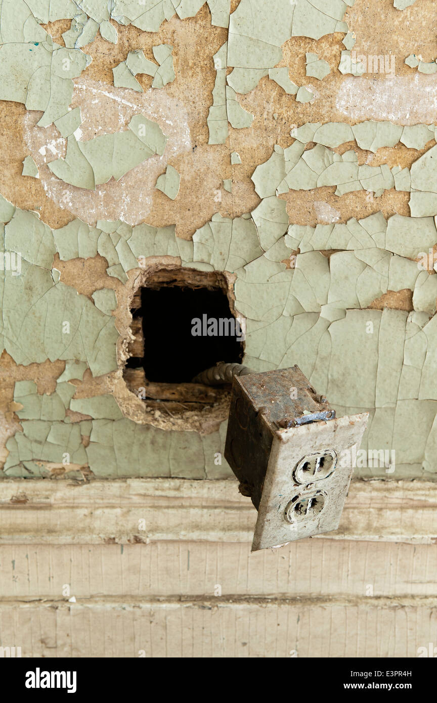Old plug socket hanging out of hole in wall with cracked wall paint - Stock Image