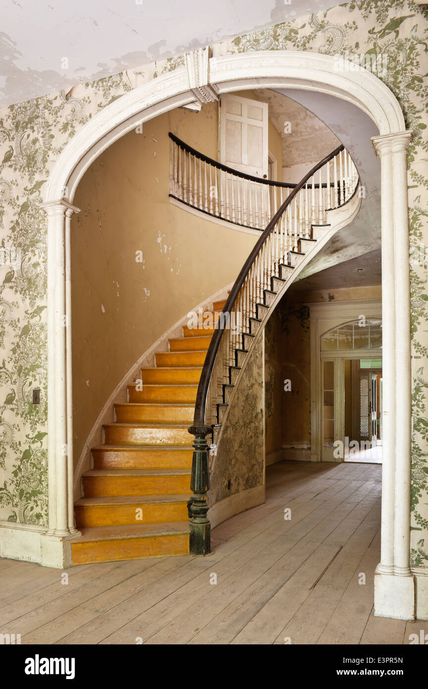 Elliptical Staircase In Hallway With Arch, Peeling Patterned Wallpaper And  Wooden Flooring   Stock Image