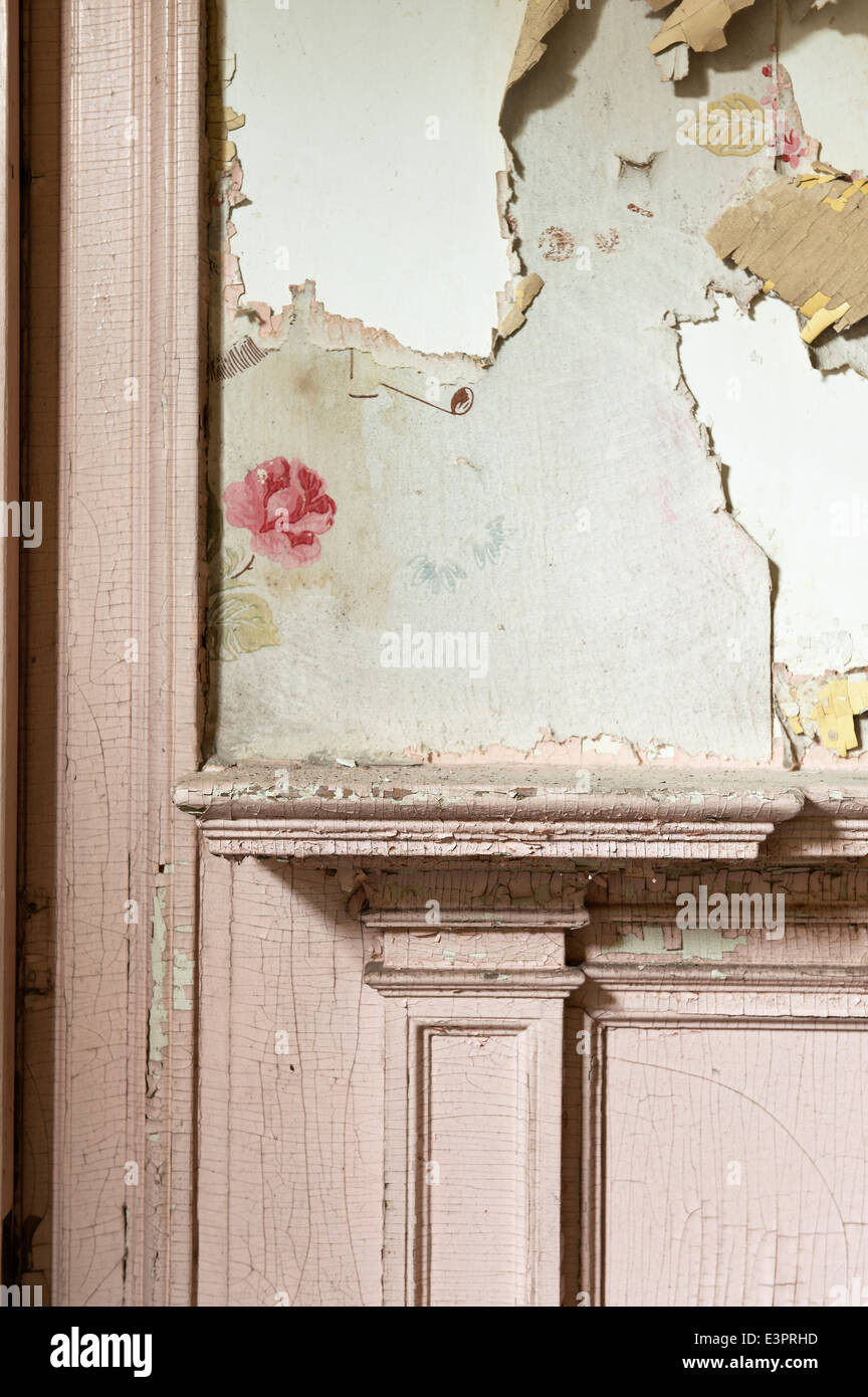 Details of peeling floral wallpaper above mantelpiece with cracked paint - Stock Image