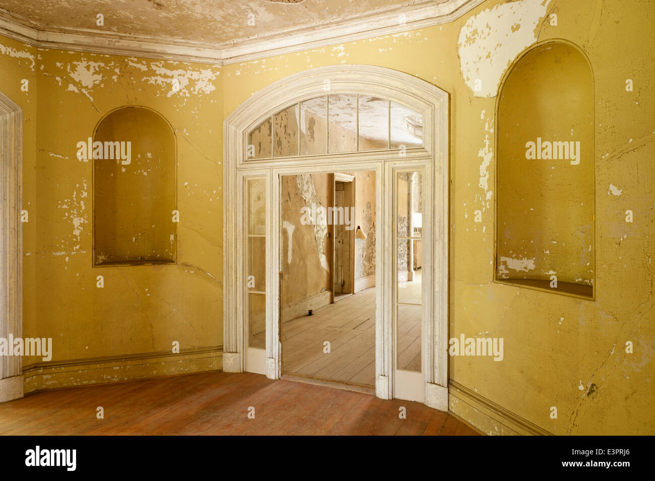 Glass door with fanlights in room with cracked wall paint and alcoves - Stock Image