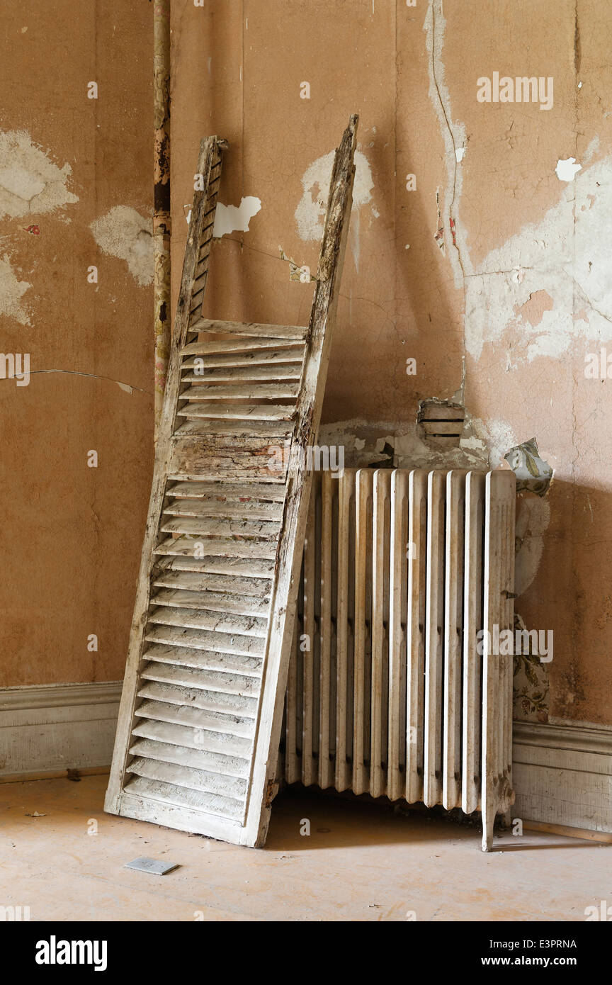 Damaged old shutter leaning against an old iron radiator by wall with cracked paint - Stock Image