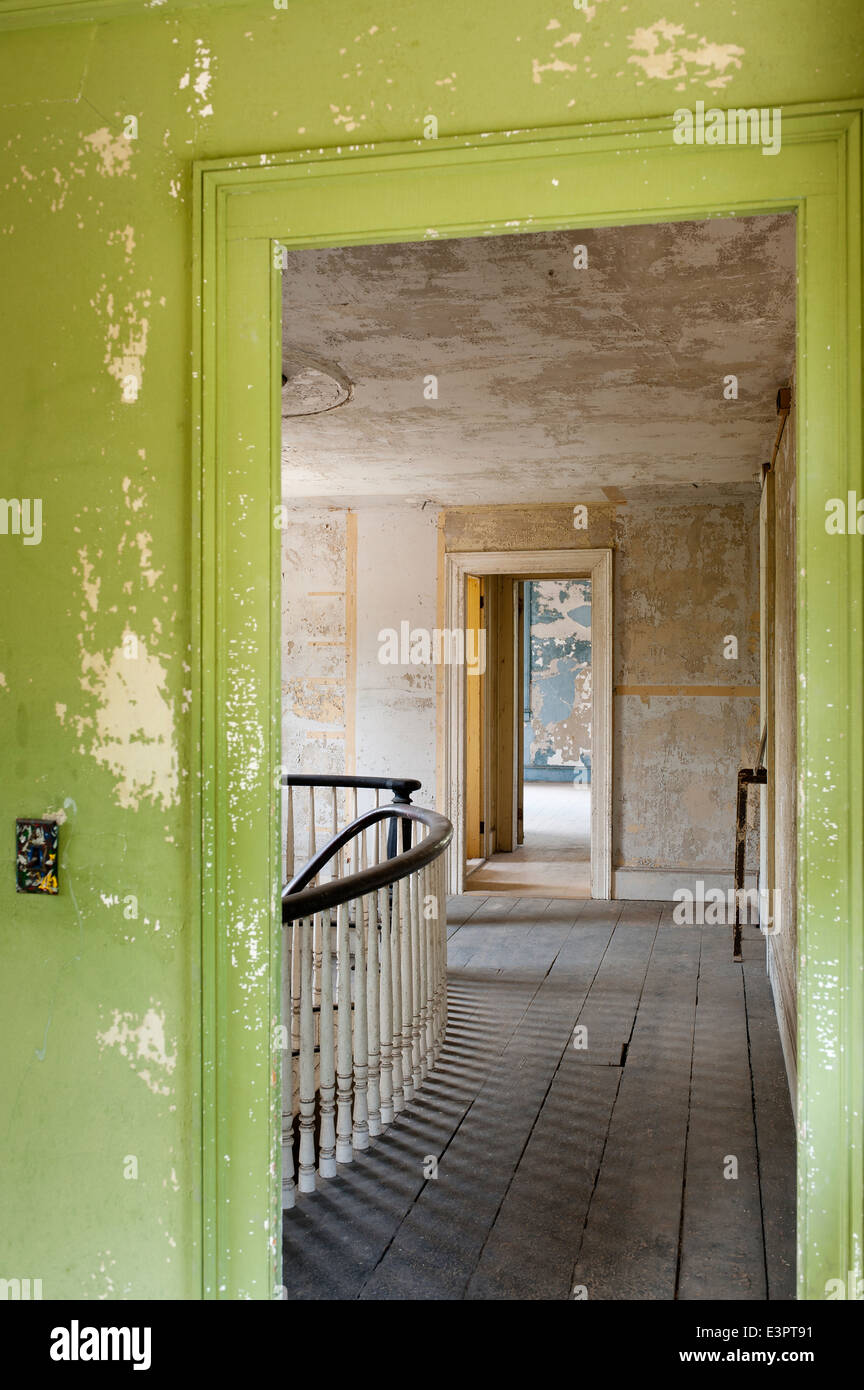View through green doorway with peeling paint work out on to empty landing in similar condition - Stock Image