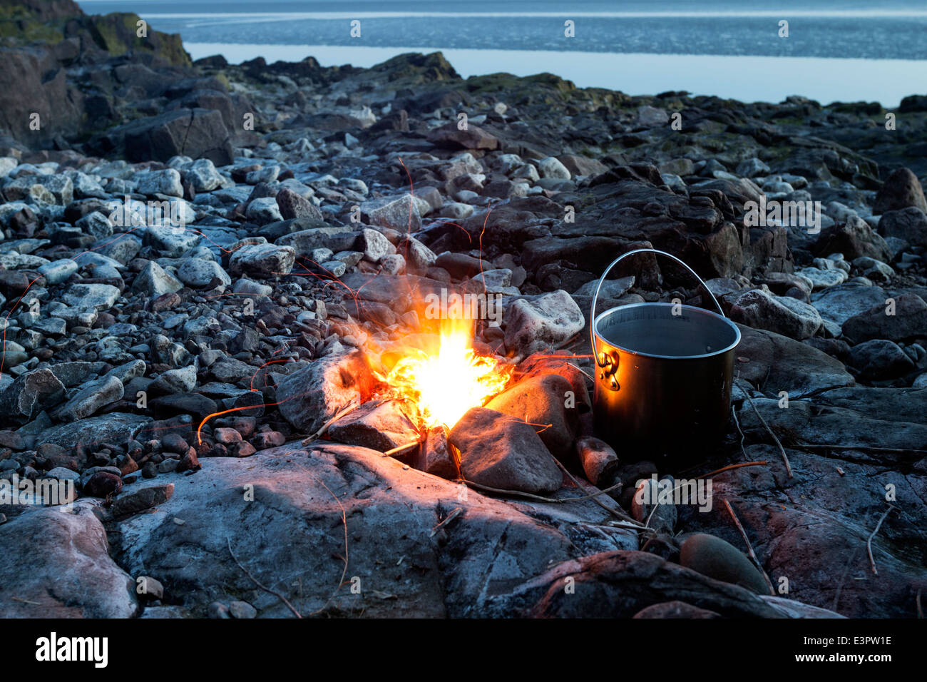 Fire with Cooking Pot on a Rocky Beach at Dusk England UK - Stock Image