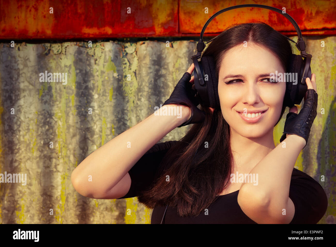 Girl with Big Headphones on Grunge Background - Stock Image