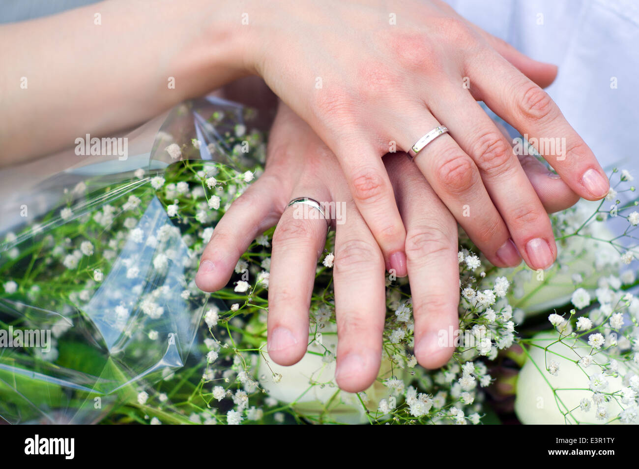 Hands of bride and groom wearing wedding silver rings near the Stock ...