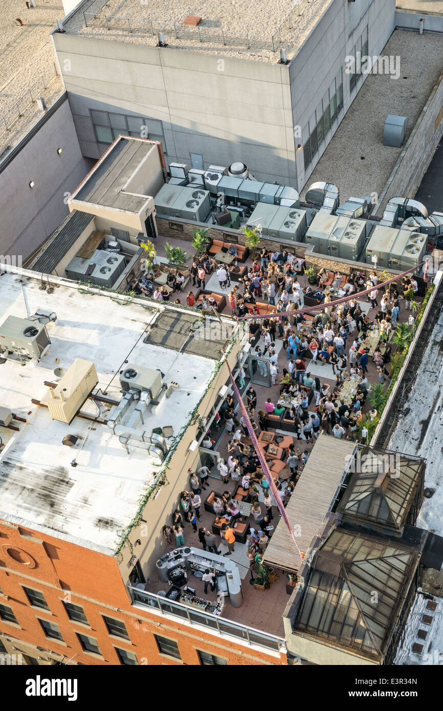 view down on crowd of young people enjoying balmy spring evening at Hells Kitchen rooftop bar New York City - Stock Image
