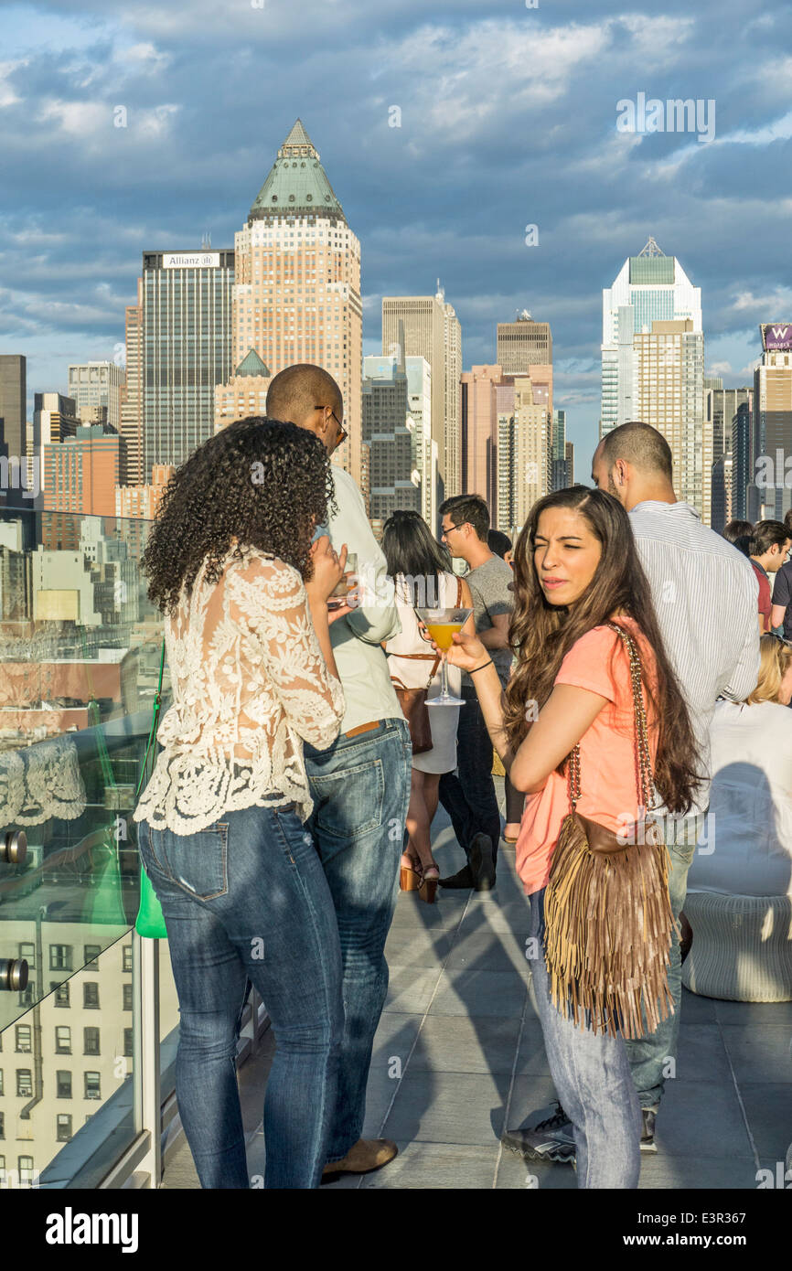 multiracial group young couples crowd railing of Ink48 Hotel rooftop bar Press Lounge enjoying sunset view of midtown - Stock Image