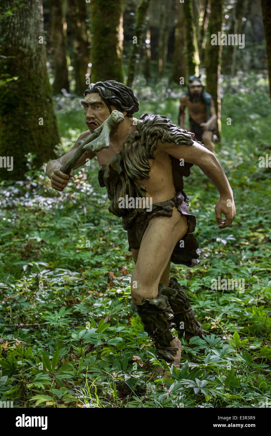 Neanderthal hunters chasing prey in forest at Prehisto Parc, theme park about prehistoric life at Tursac, Dordogne, - Stock Image