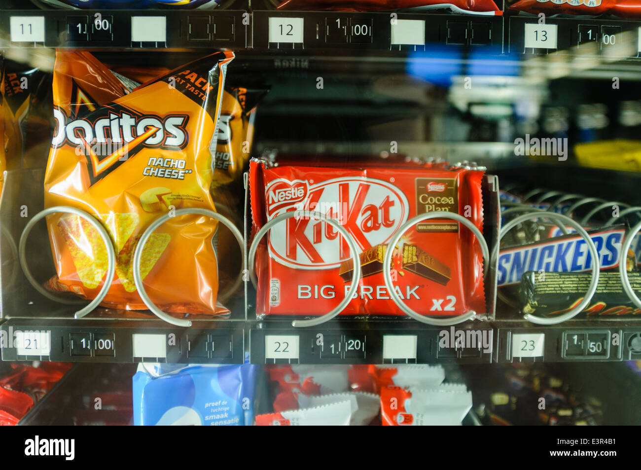 Doritos, Kitkat, Mars and Snickers on sale in a vending machine - Stock Image