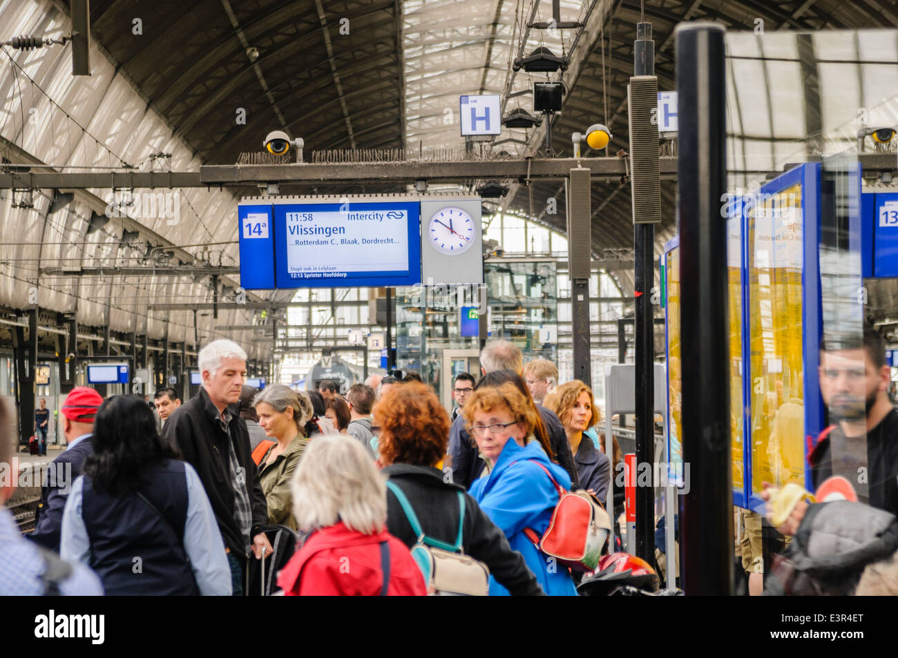 Passengers wait on a platform in Amsterdam Centraal Station for a train Stock Photo
