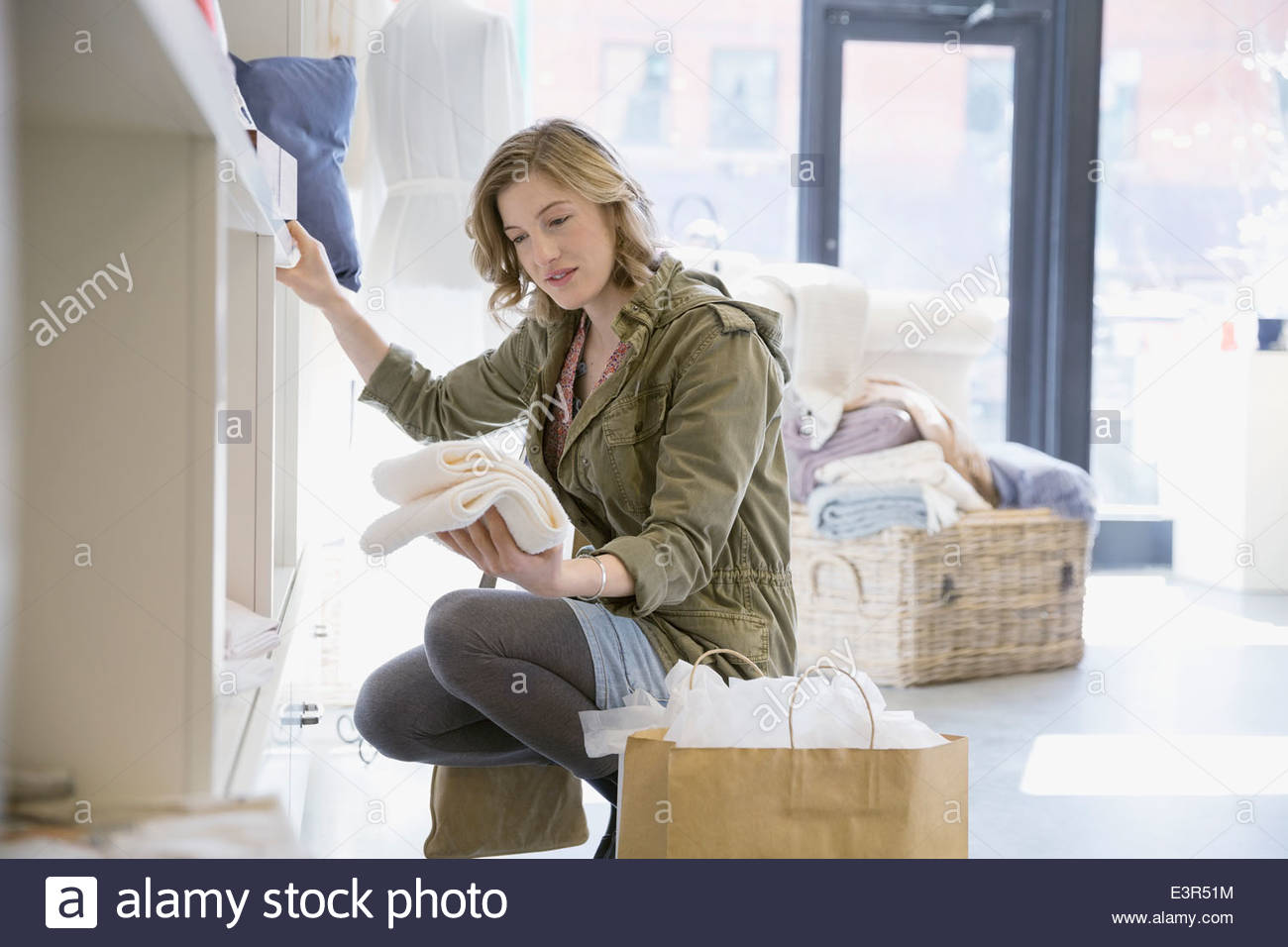 Woman looking at towels in shop - Stock Image