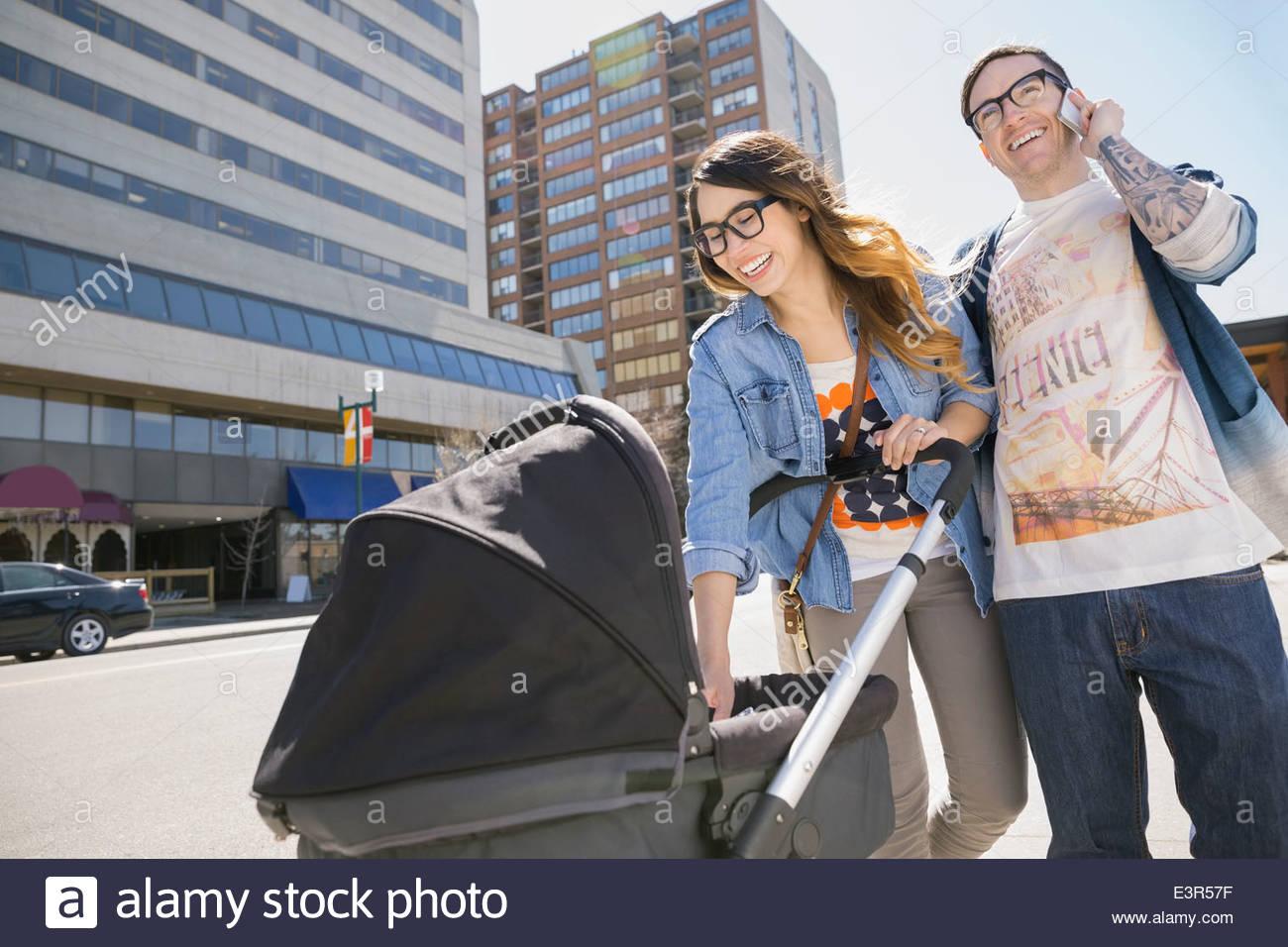Hipster couple pushing stroller on sunny urban street - Stock Image