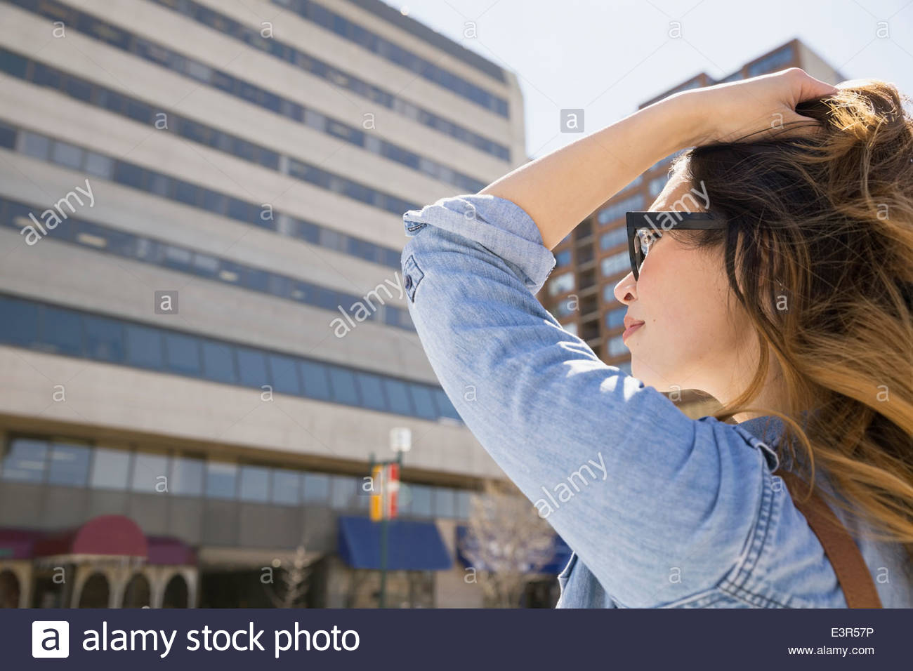 Woman with hand in hair on sunny urban street - Stock Image