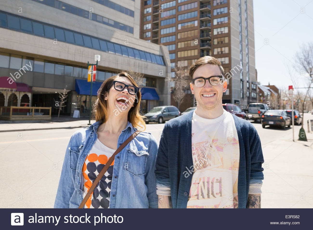 Hipster couple laughing on sunny urban street - Stock Image