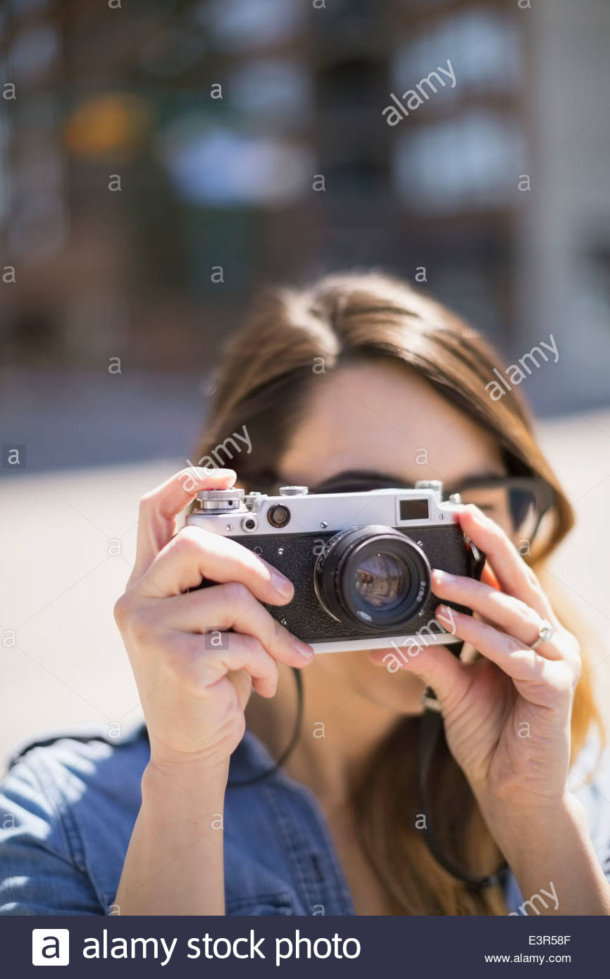 Close up of woman using camera - Stock Image