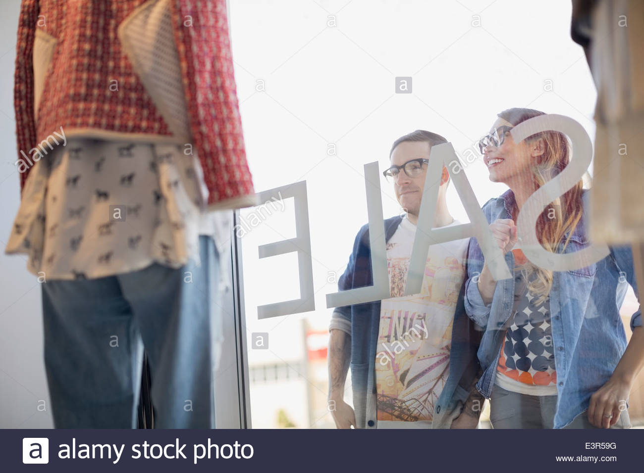 Hipster couple window shopping at storefront - Stock Image