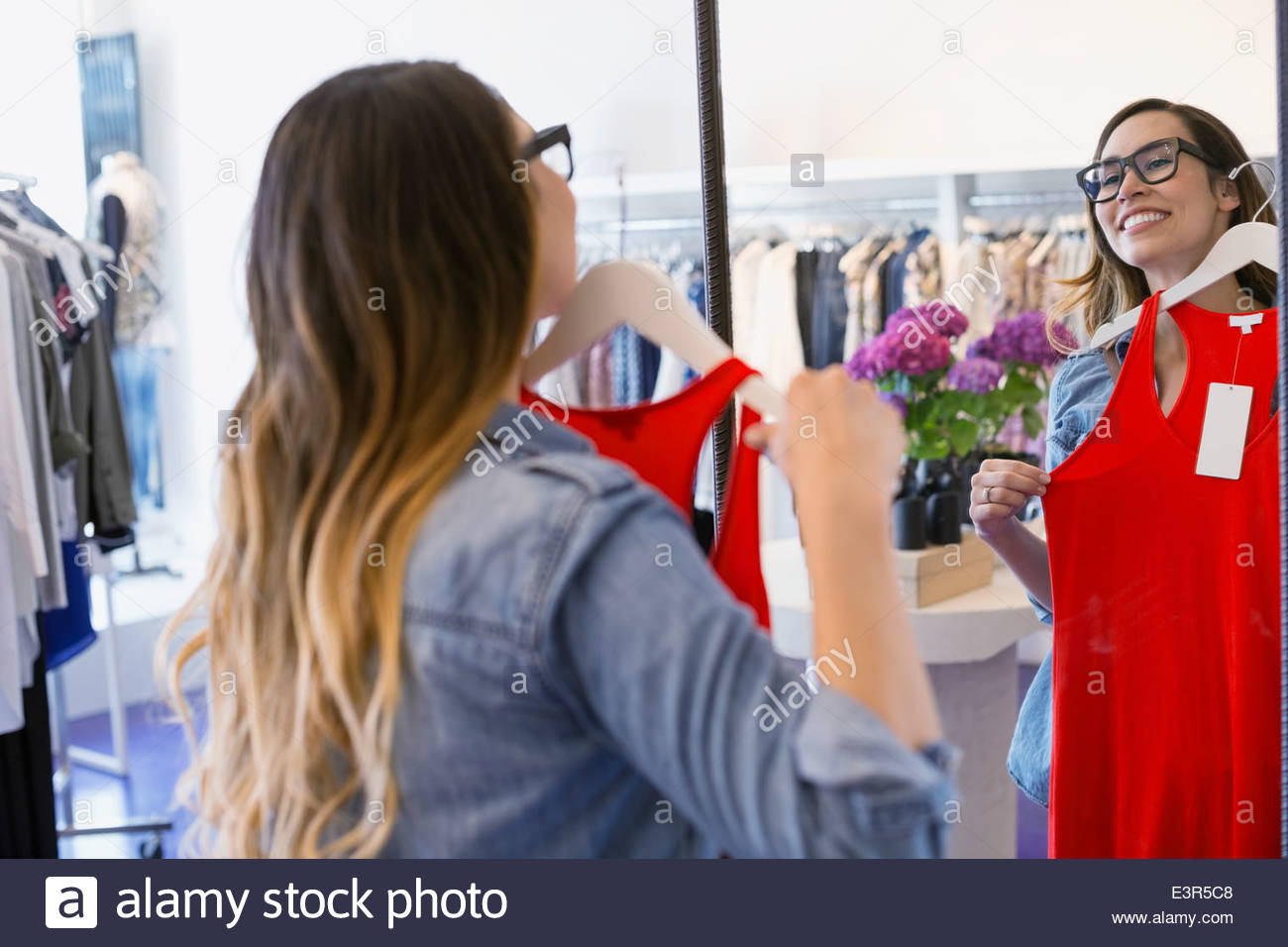 Woman holding tank-top in clothing store - Stock Image