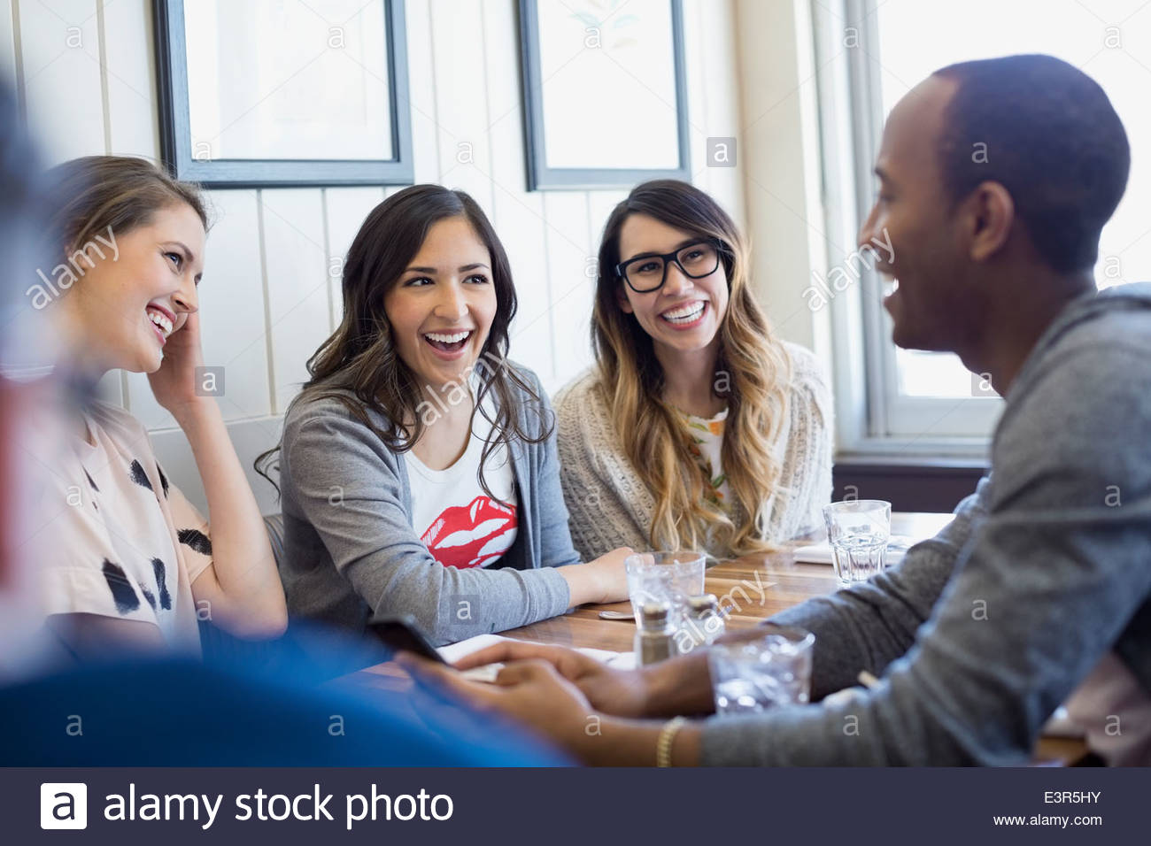 Friends talking at bistro - Stock Image