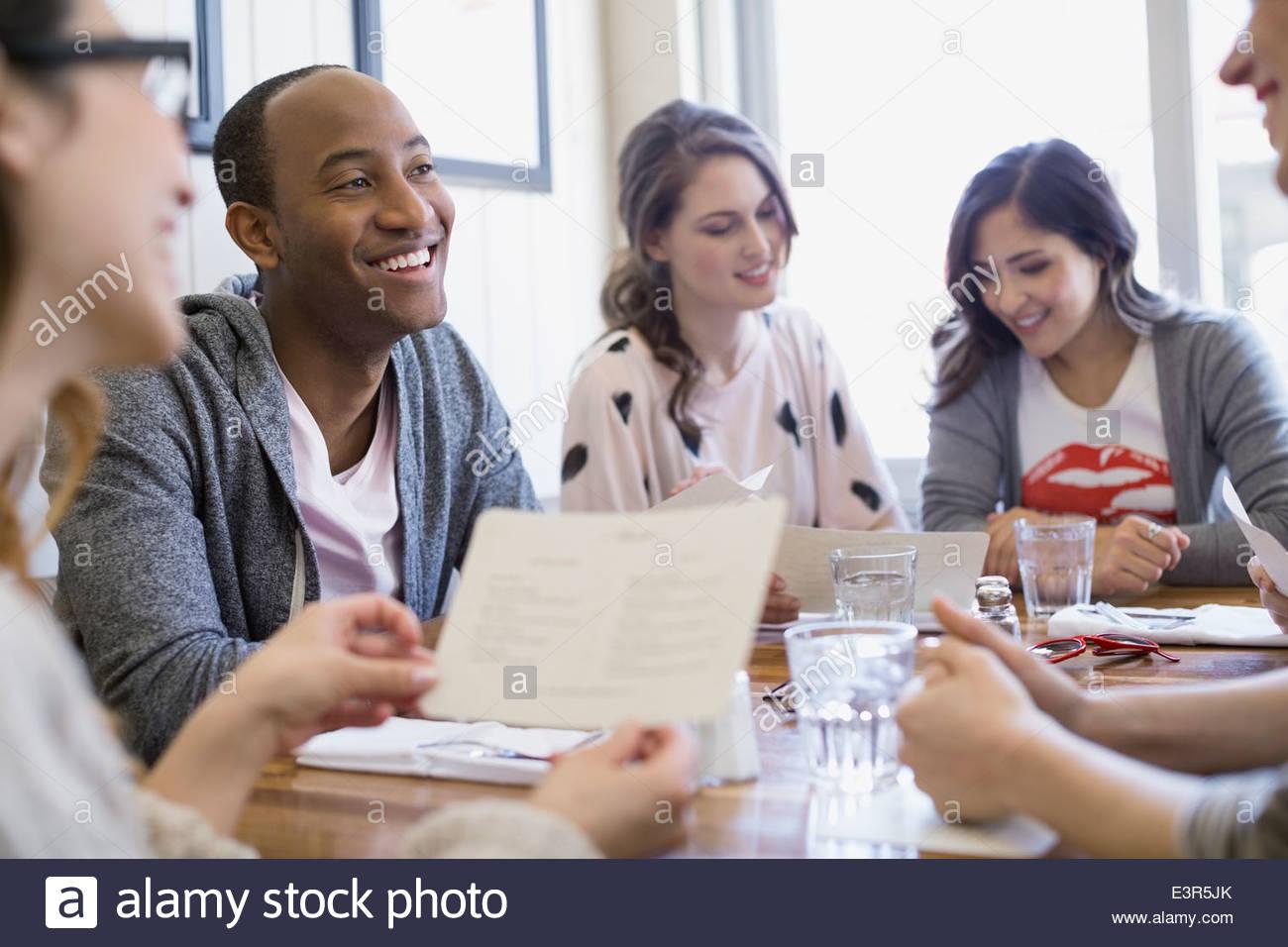 Friends looking at menus in bistro - Stock Image