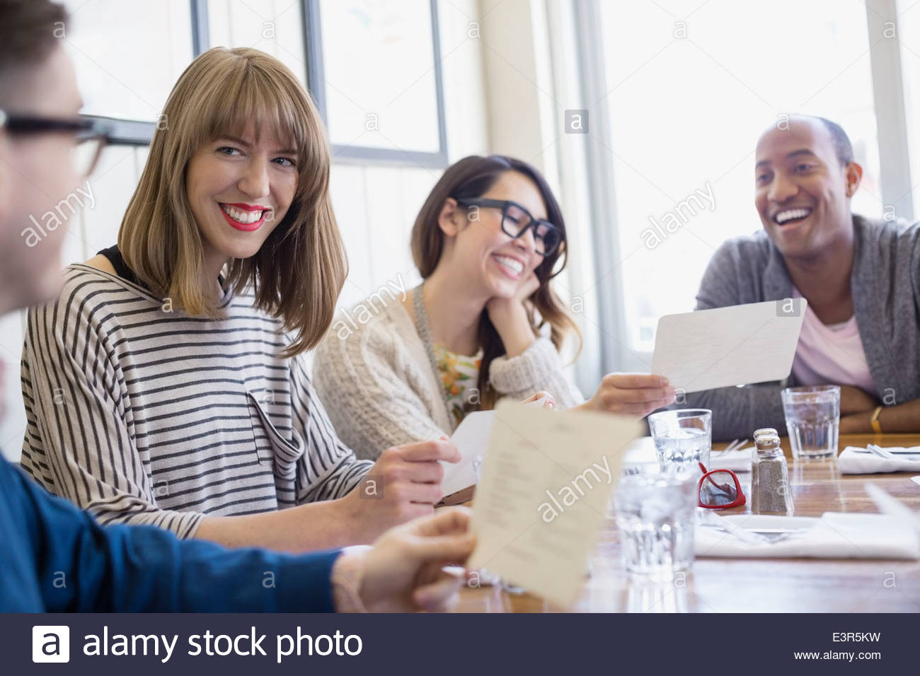Friends looking at menus at bistro table - Stock Image
