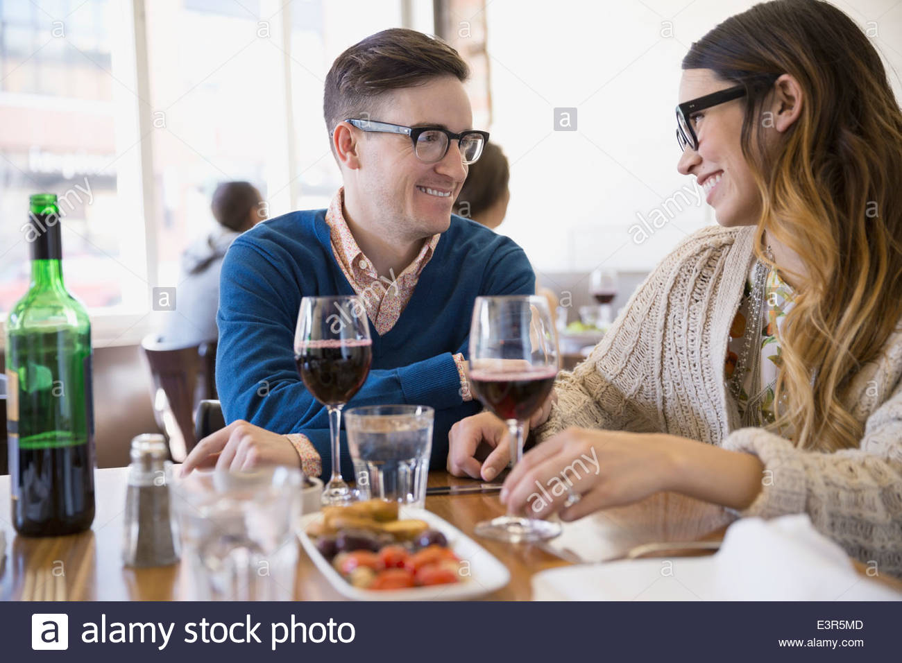 Couple enjoying appetizer and wine at bistro - Stock Image