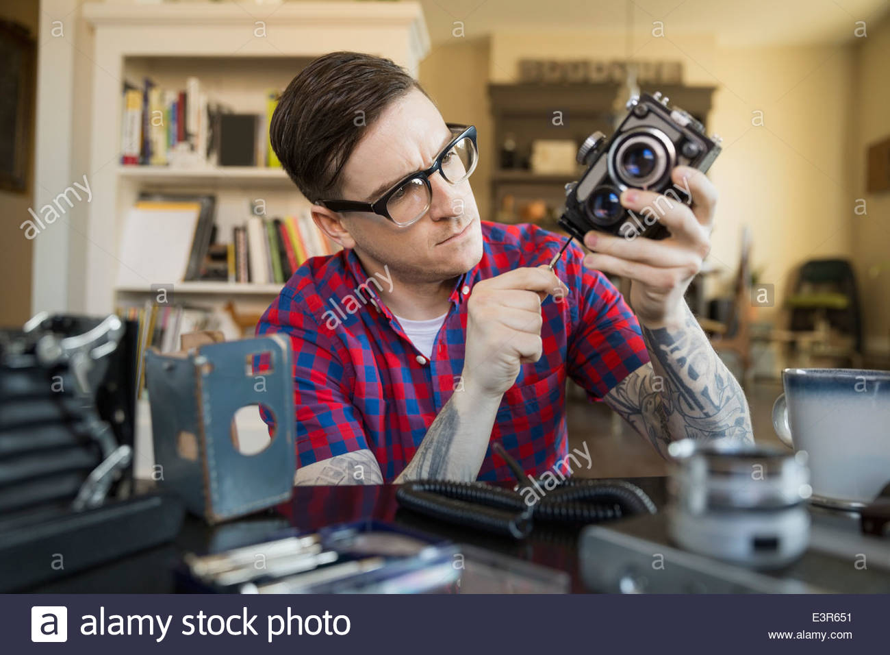 Man repairing antique camera in living room - Stock Image