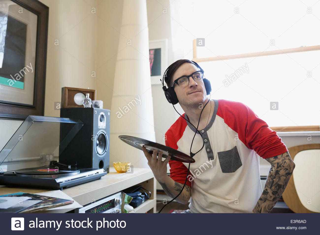 Man with headphones listening to records - Stock Image