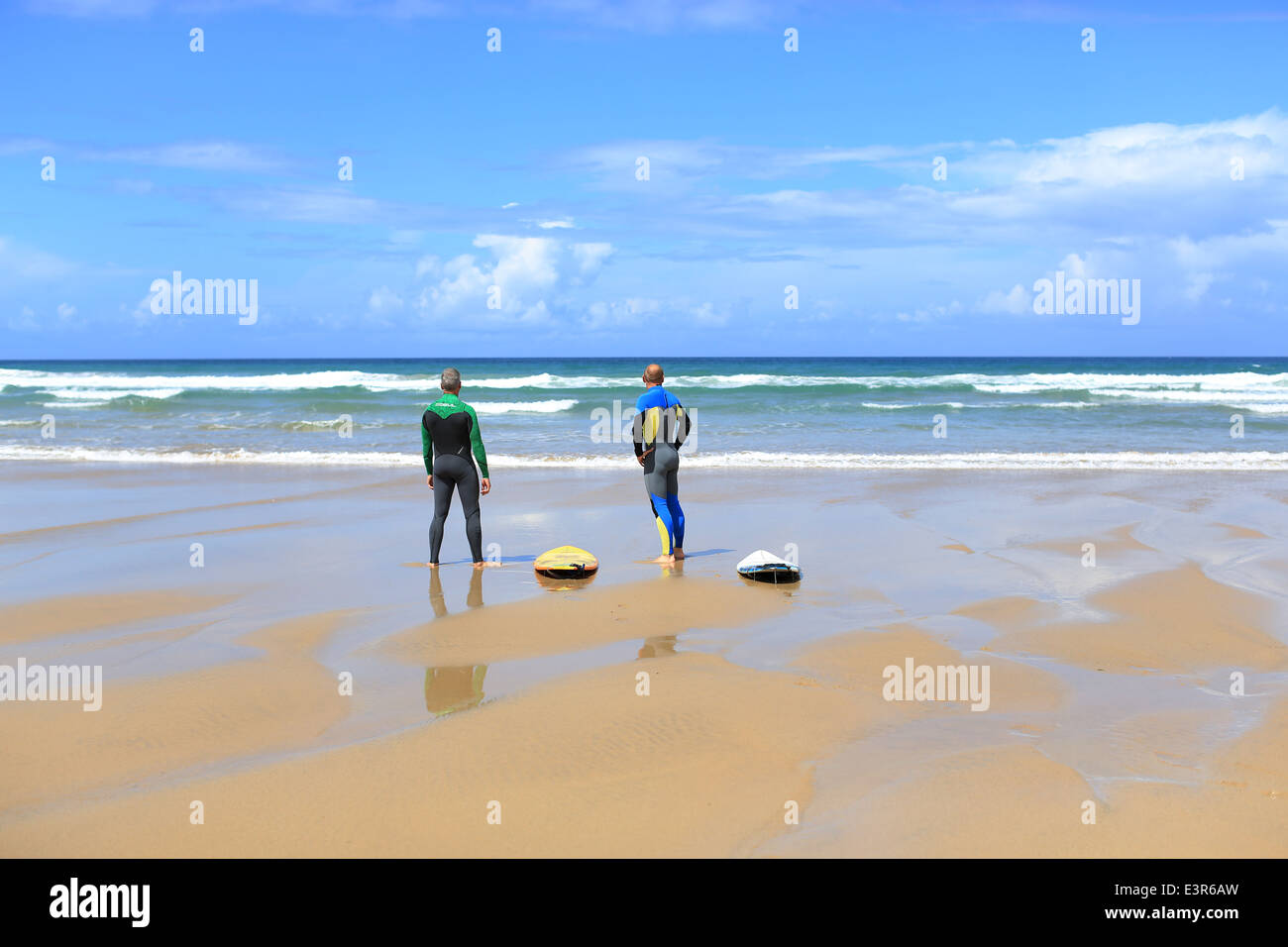 Silver surfers, two middle aged men with surf boards on an empty beach on a sunny day with blue sky - Stock Image
