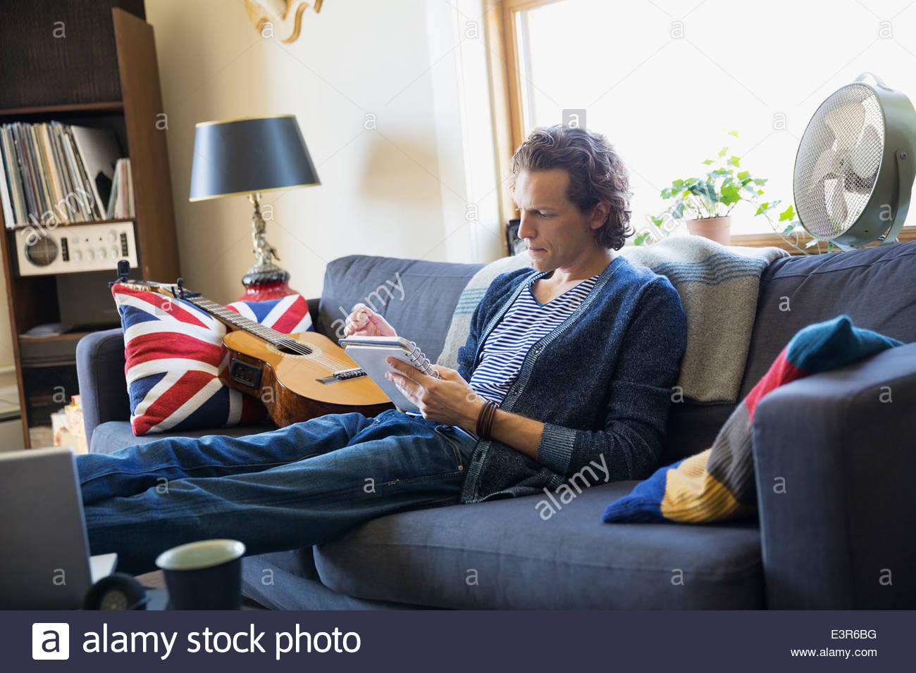 Man with guitar writing music on sofa - Stock Image