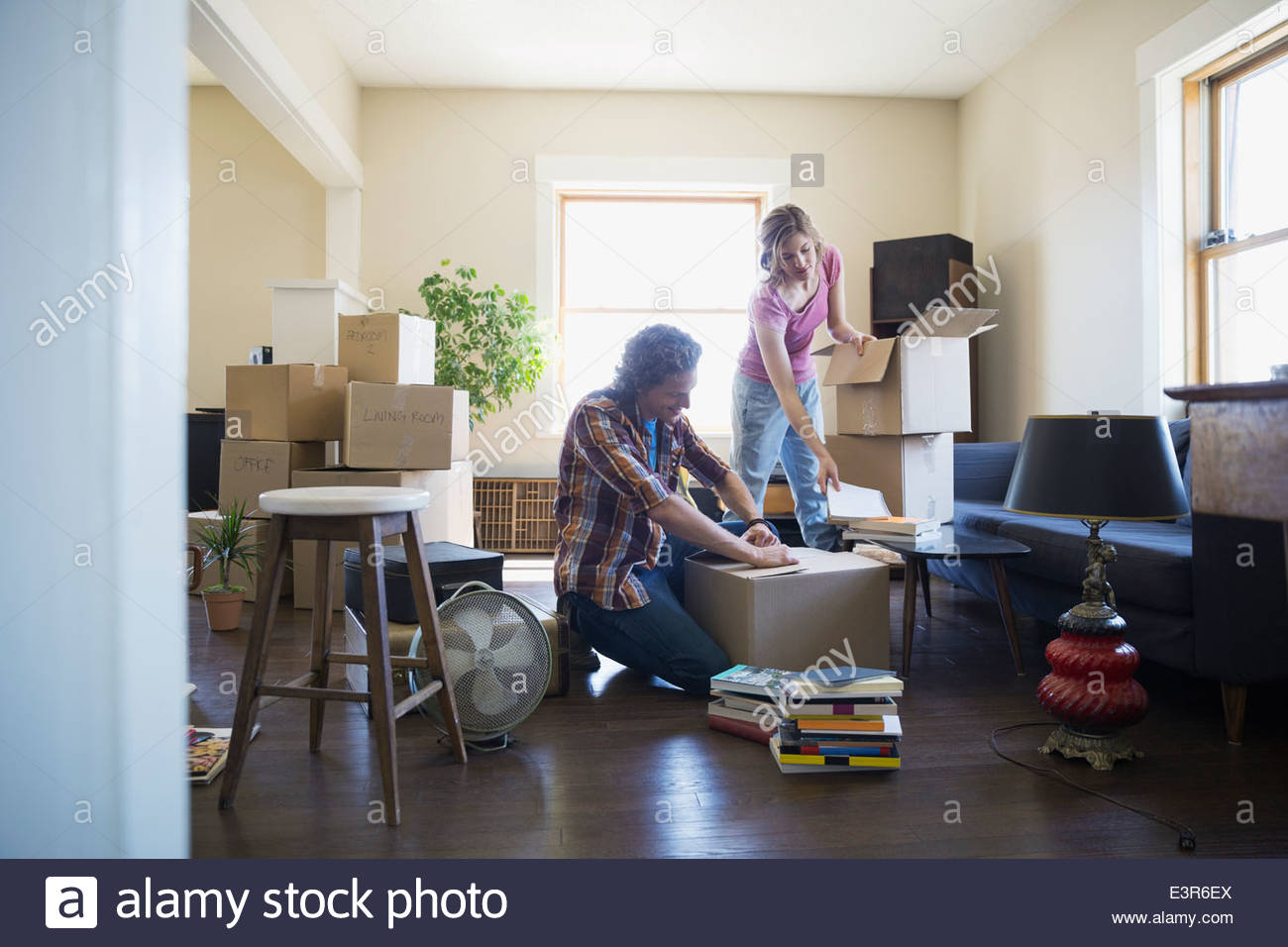 Couple packing moving boxes in living room - Stock Image