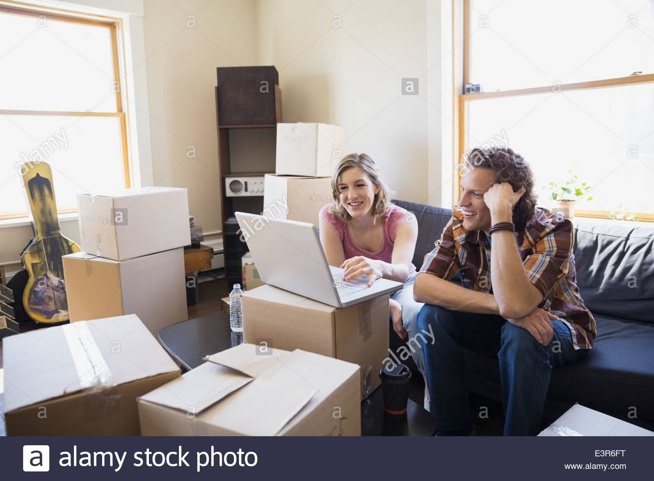 Couple with laptop on sofa surrounded by boxes - Stock Image