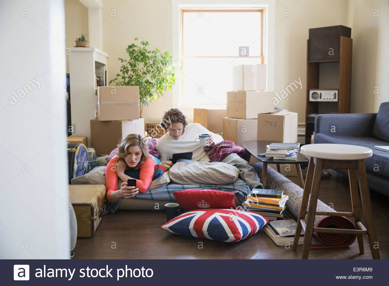 Couple using technology surrounded by moving boxes - Stock Image