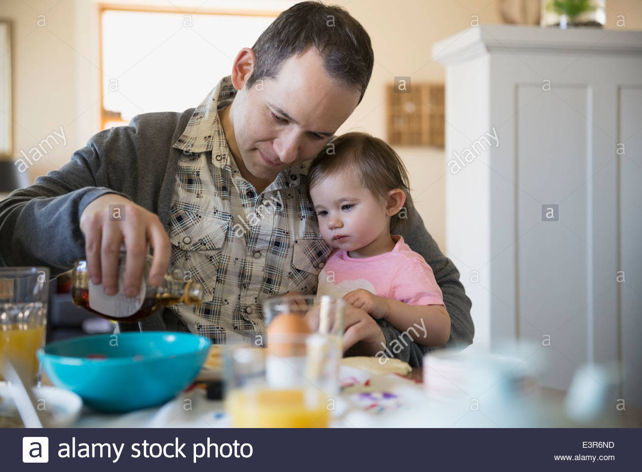 Father and baby daughter enjoying breakfast at table - Stock Image