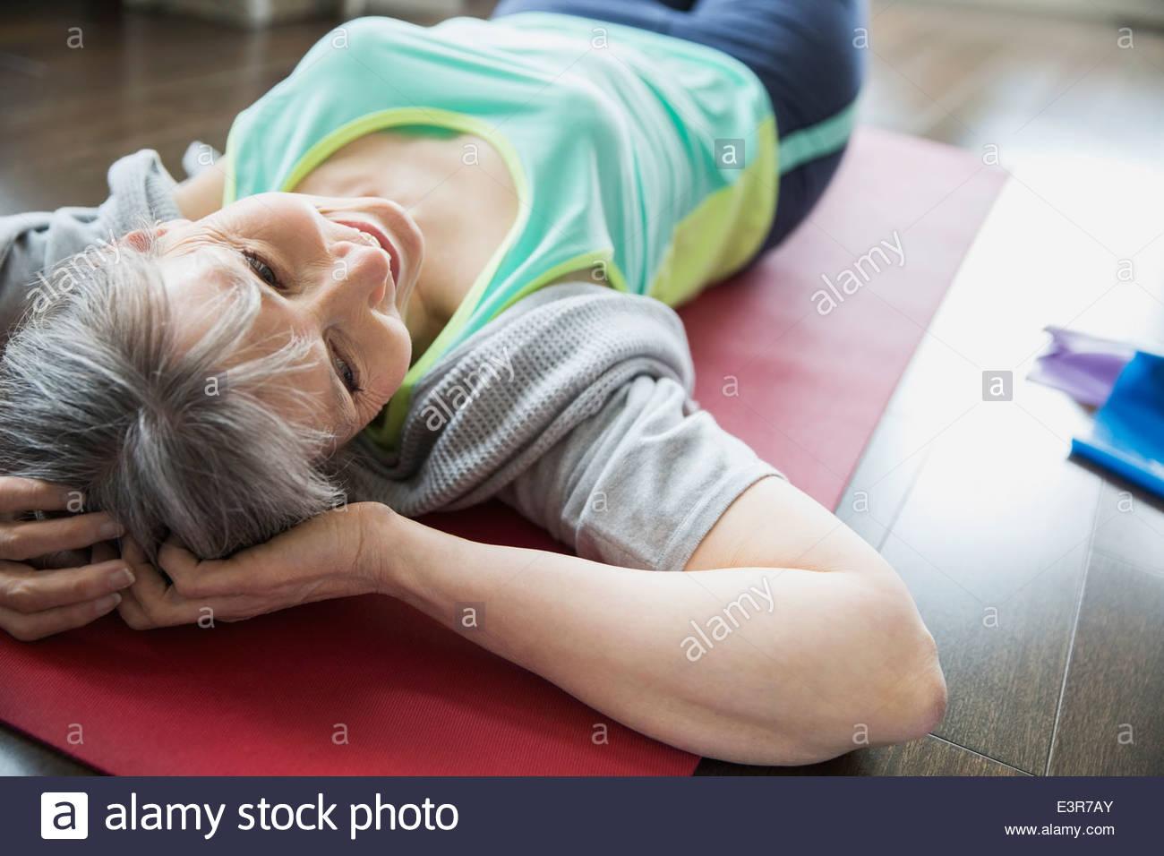 Woman laying on yoga mat - Stock Image