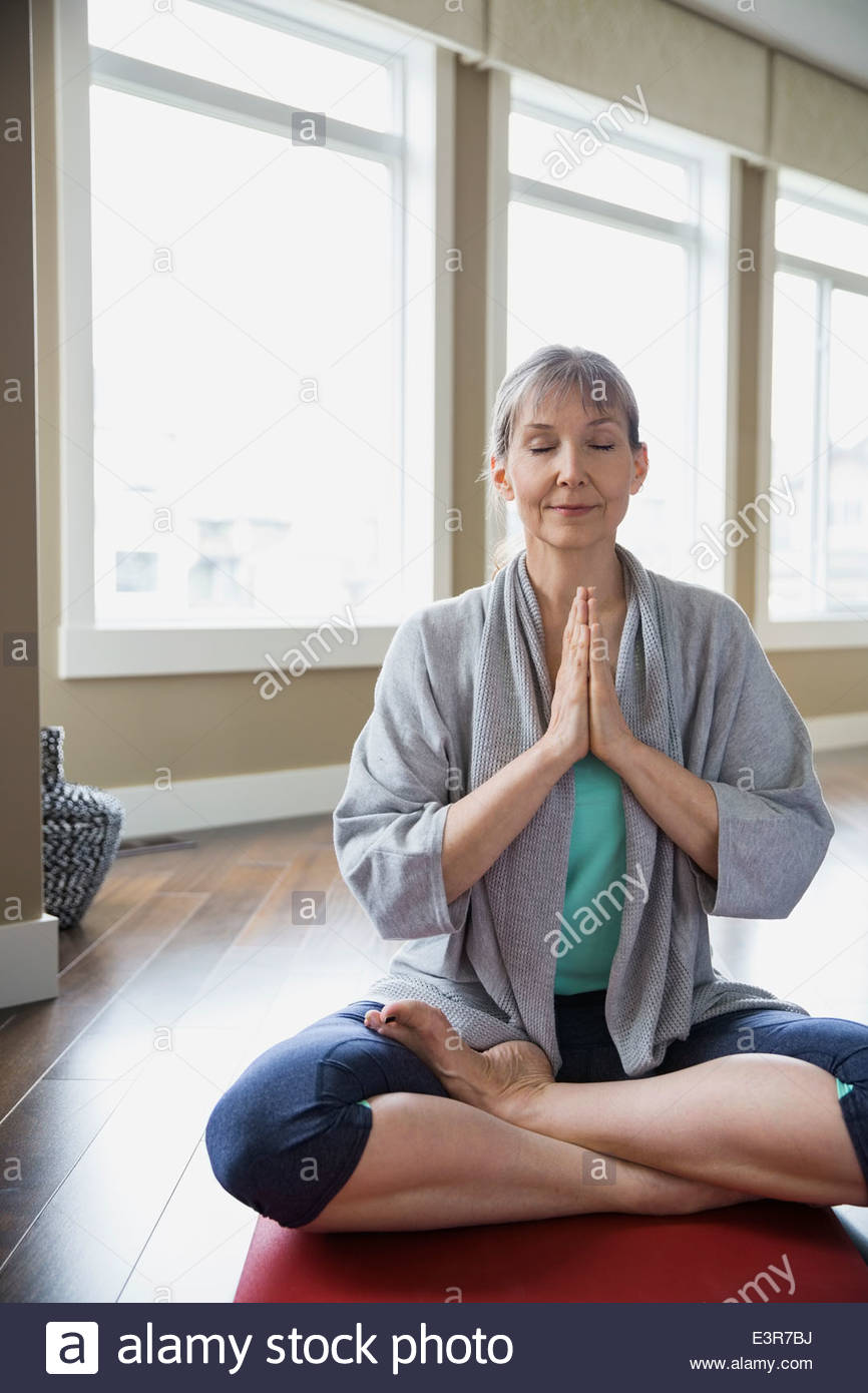 Woman meditating in living room - Stock Image