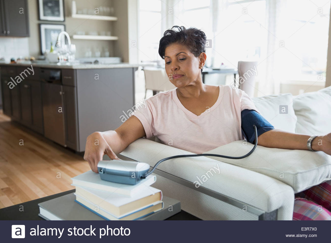 Woman checking blood pressure in living room - Stock Image