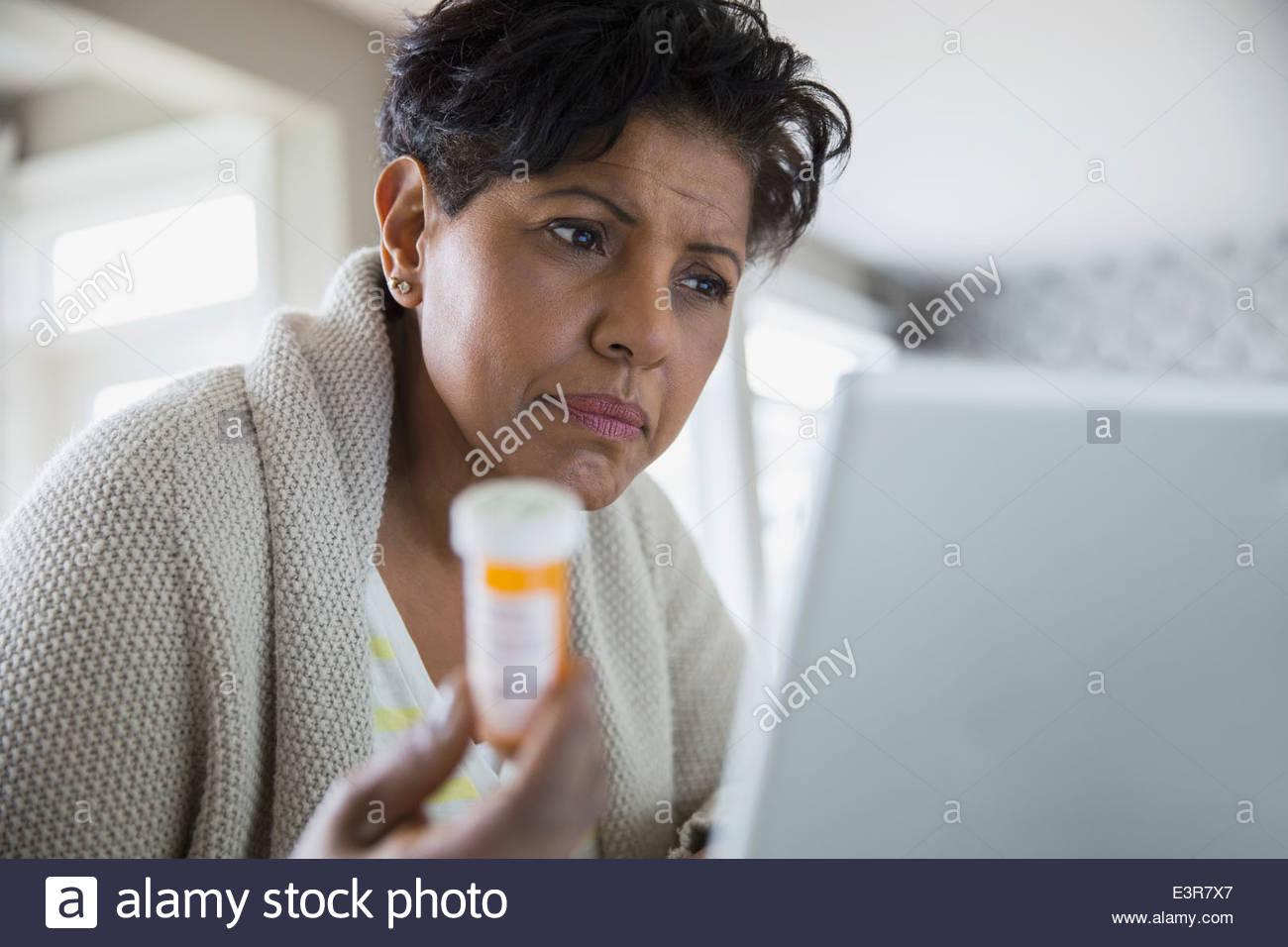 Concerned woman holding prescription bottle at laptop - Stock Image