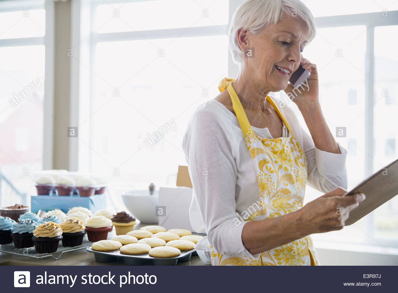 Woman on cell phone baking cupcakes in kitchen - Stock Image
