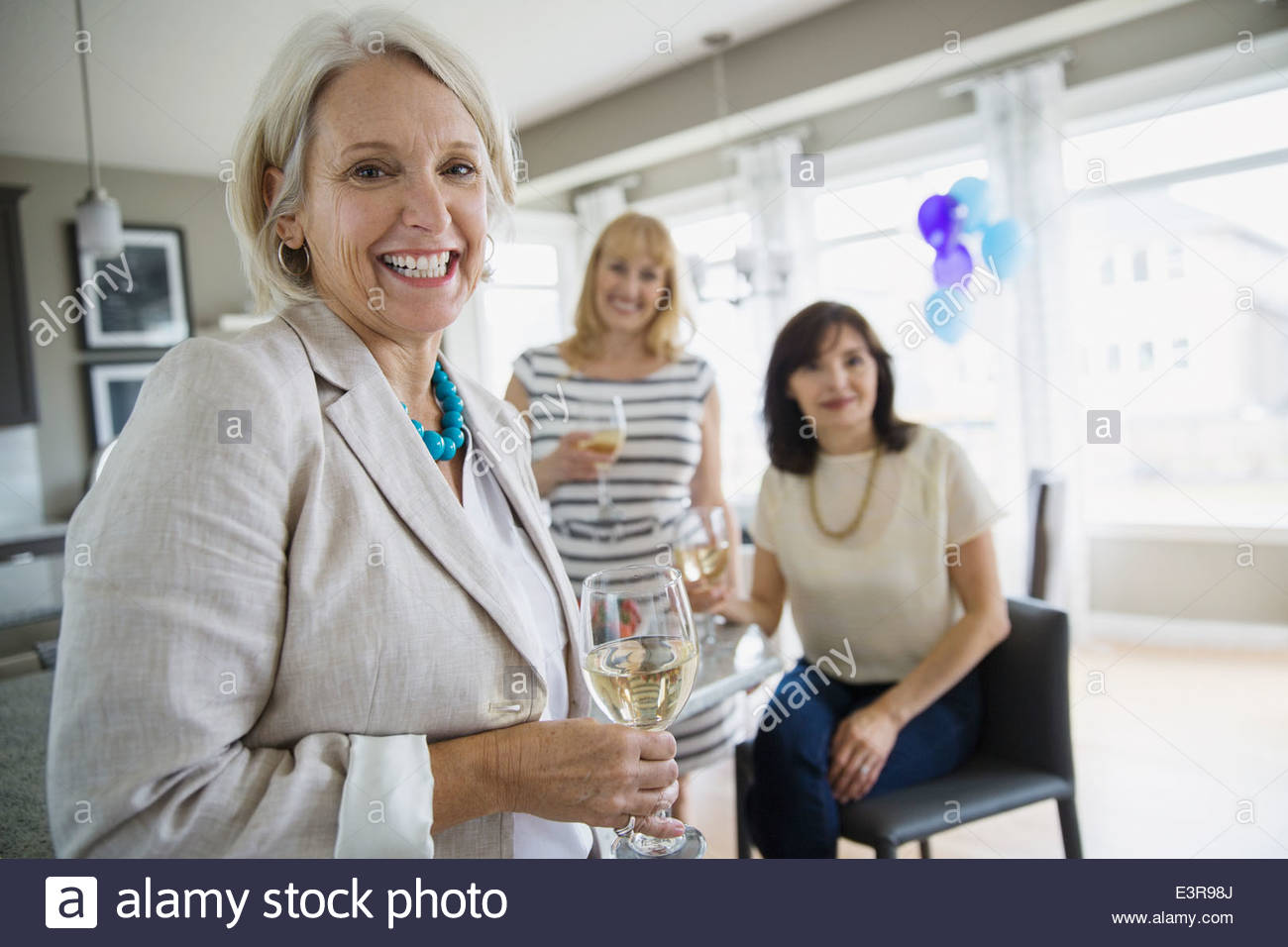 Women drinking wine at party - Stock Image