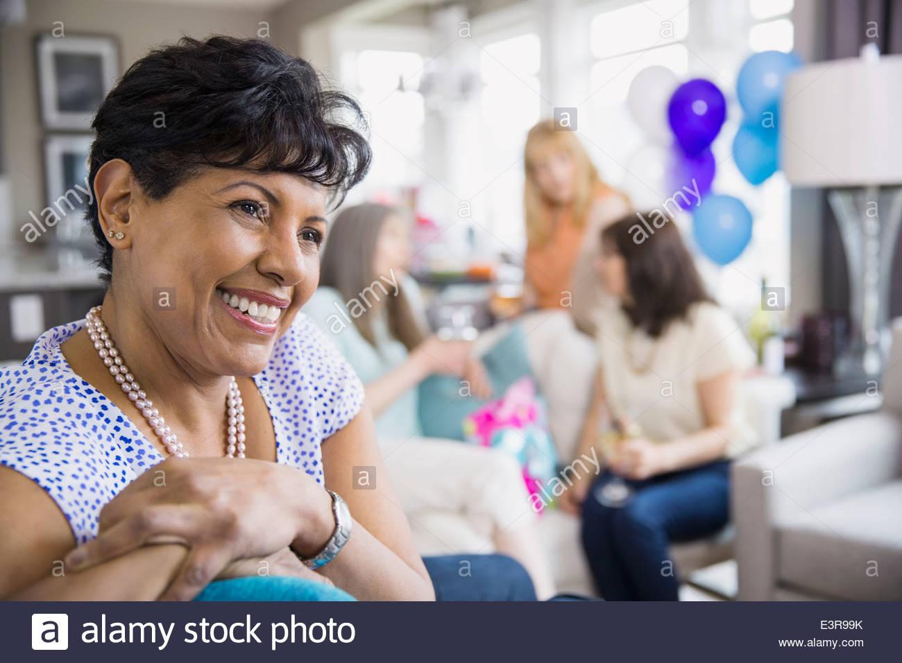 Smiling woman enjoying birthday party - Stock Image