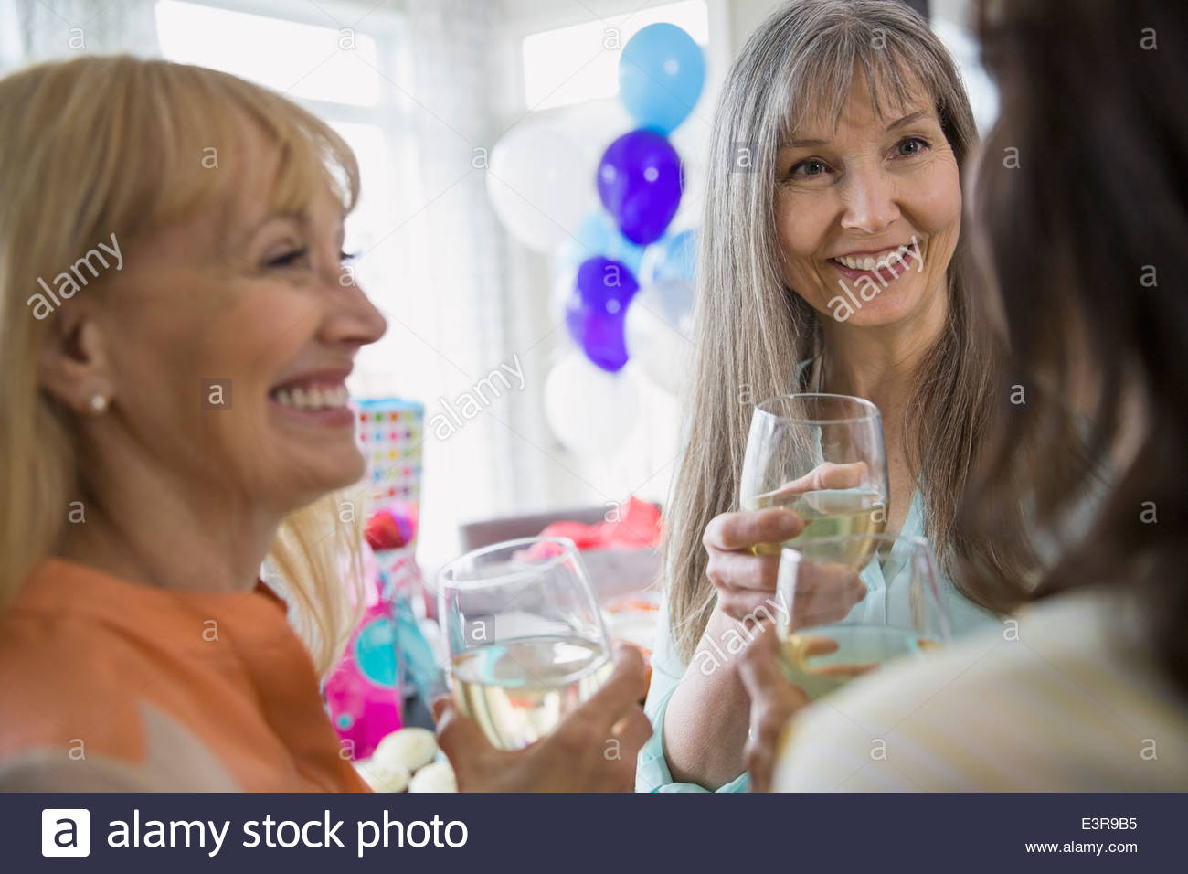 Women talking and drinking white wine at party - Stock Image