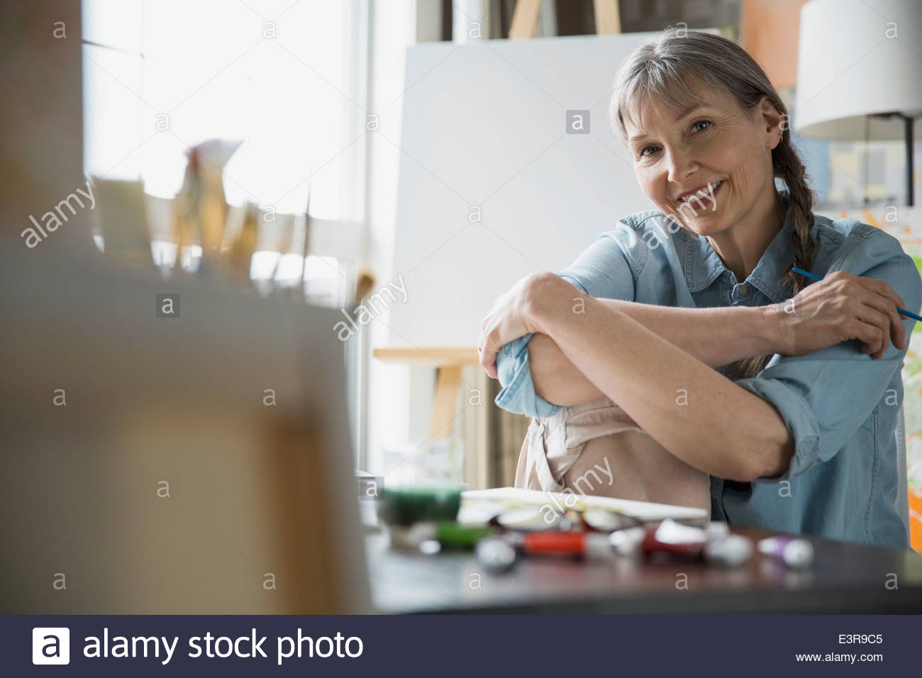 Portrait of smiling woman painting at table - Stock Image