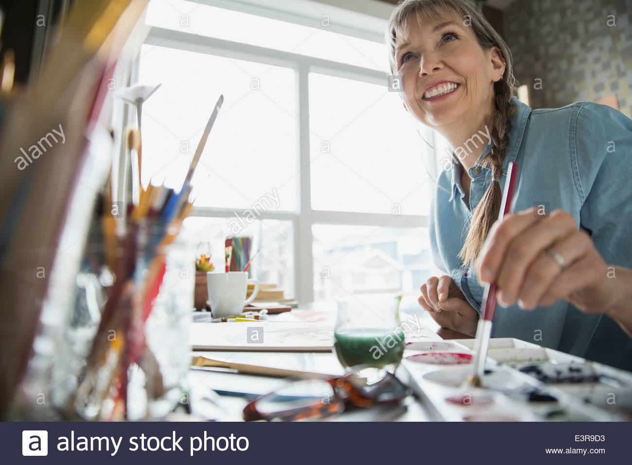 Woman painting at desk - Stock Image
