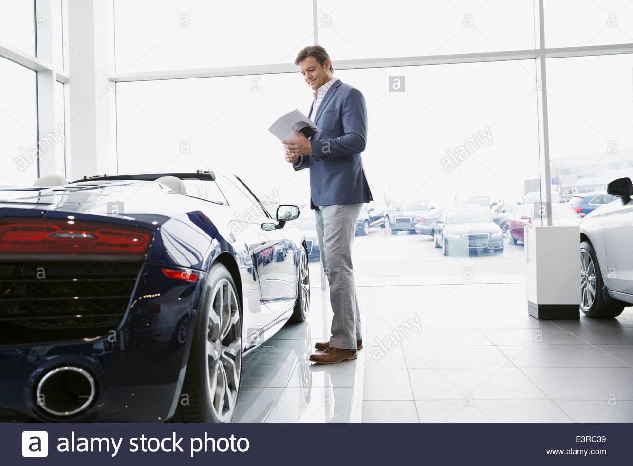 Man looking at convertible in car dealership showroom Stock Photo