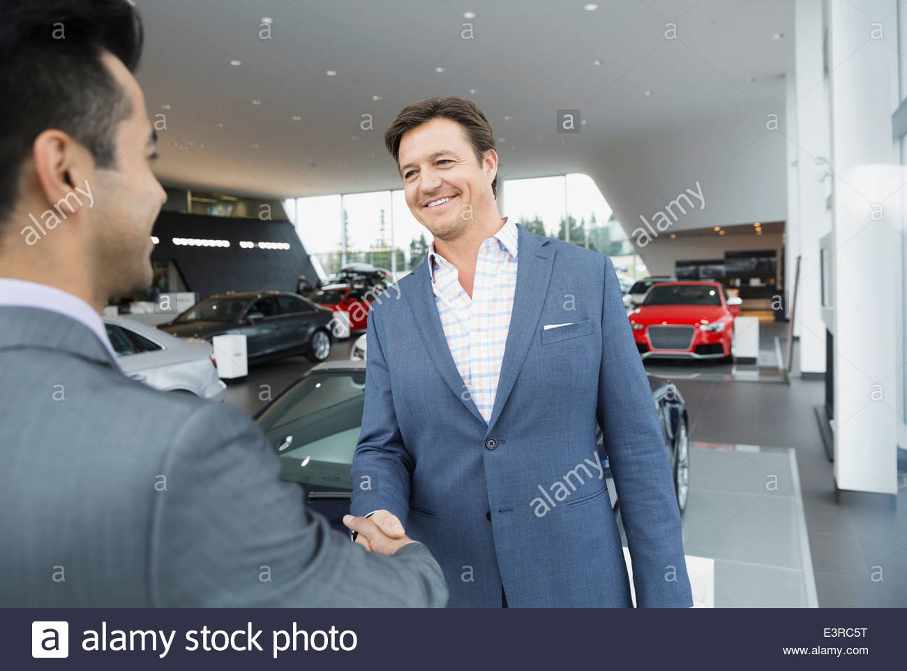 Salesman and man handshaking in car dealership showroom - Stock Image