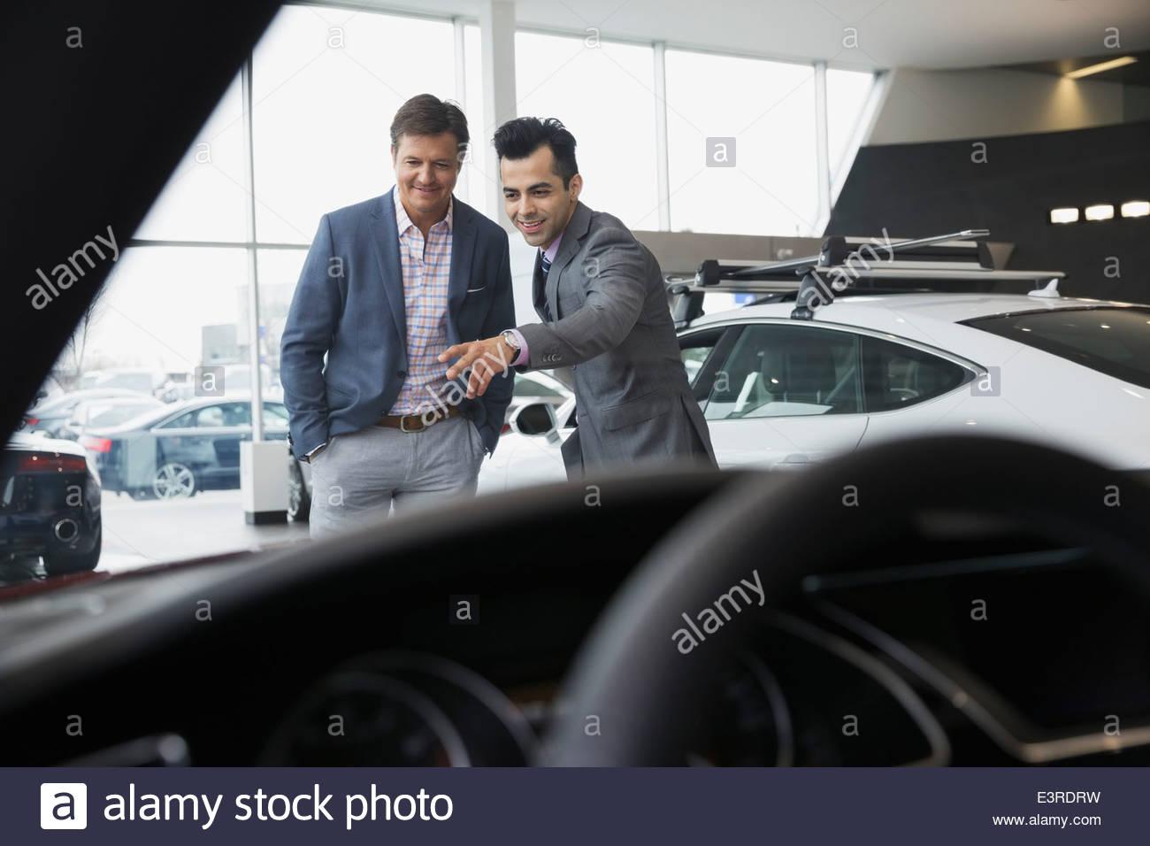 Salesman talking to man in car dealership showroom - Stock Image