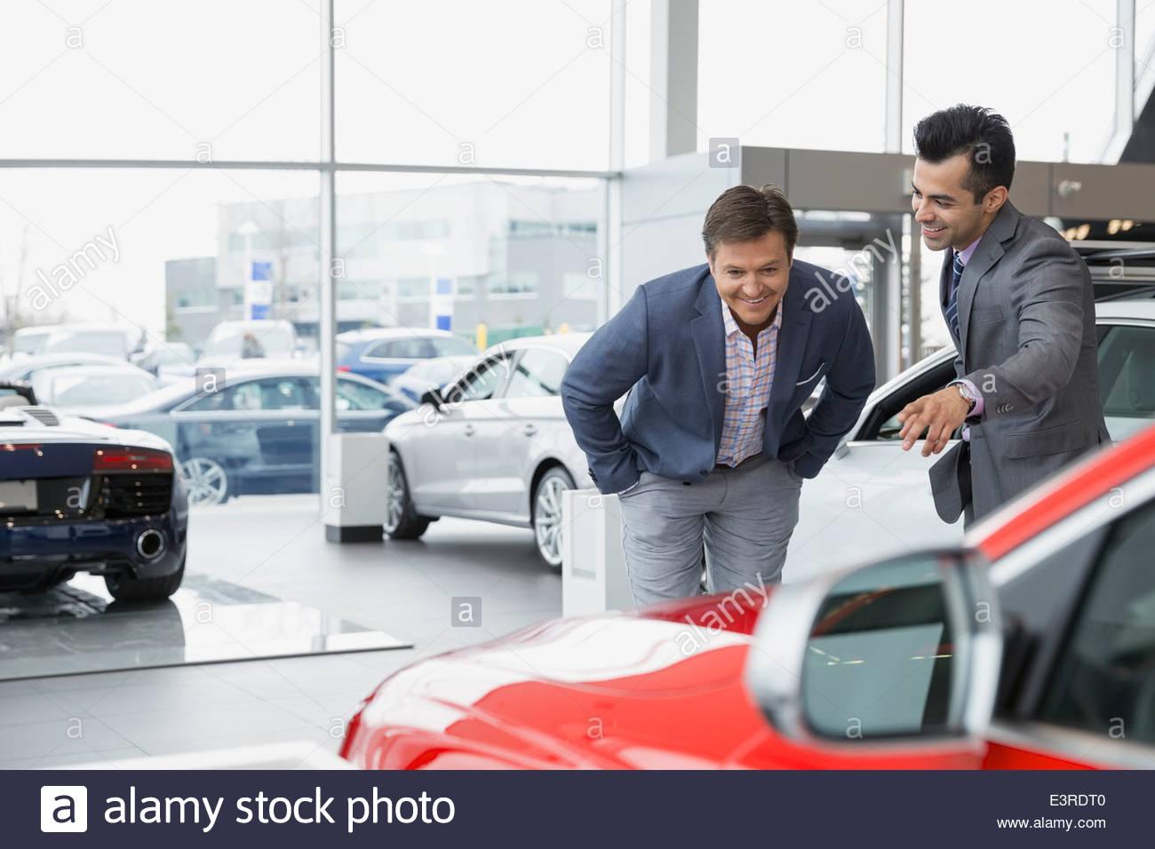 Salesman showing man car in dealership showroom - Stock Image