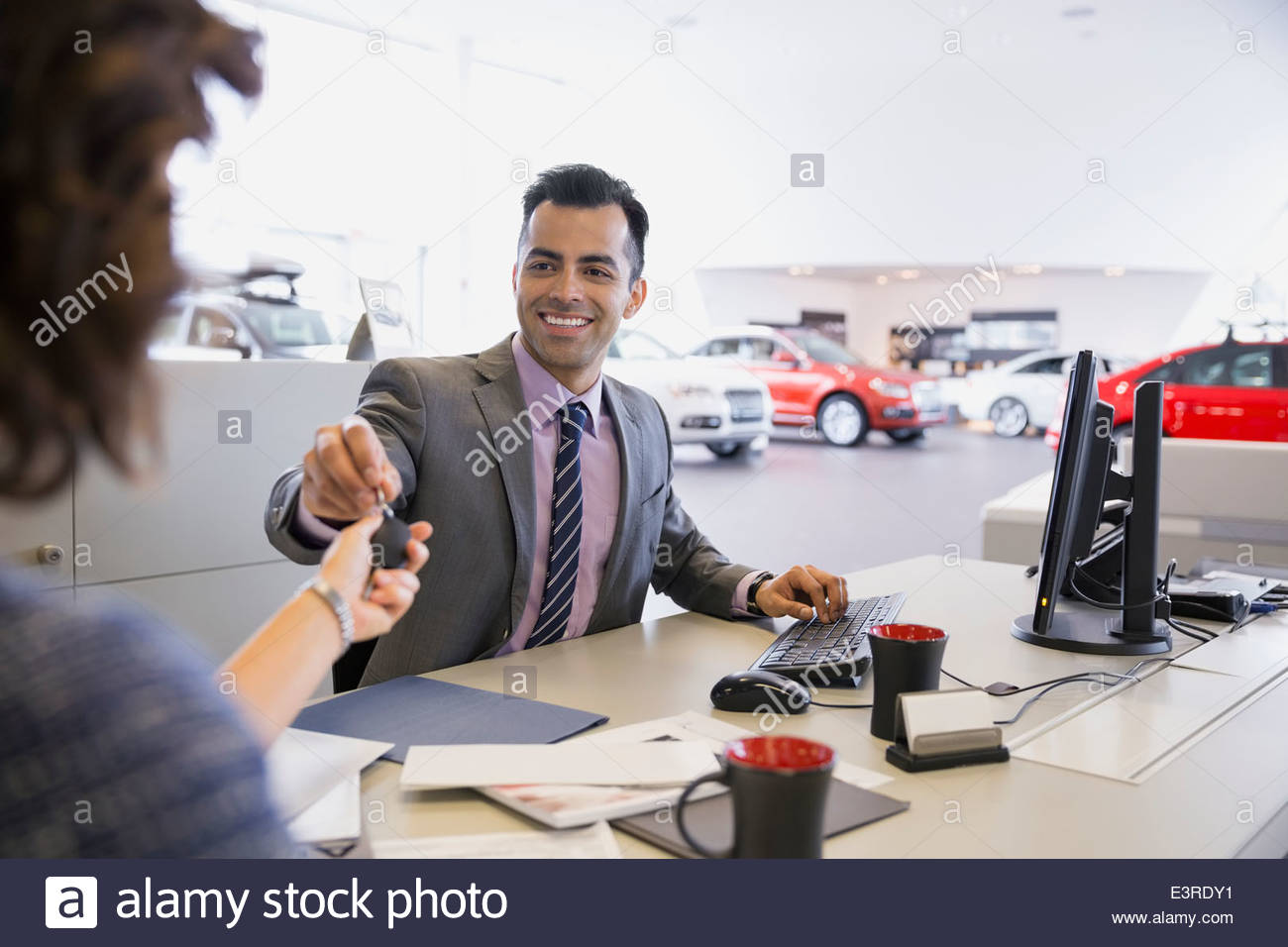 Salesman giving keys to woman in car dealership - Stock Image