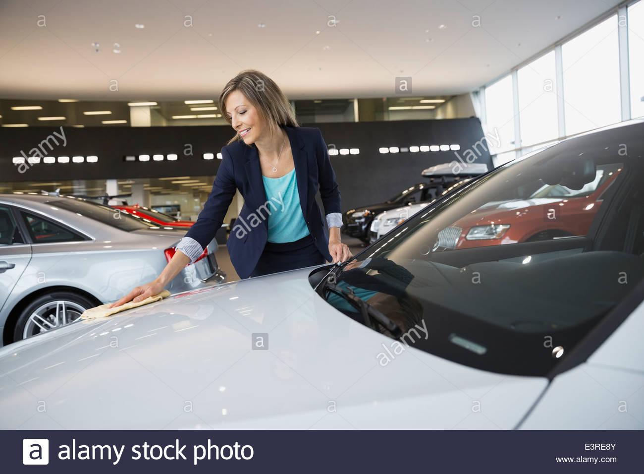 Saleswoman wiping down car in car dealership showroom - Stock Image