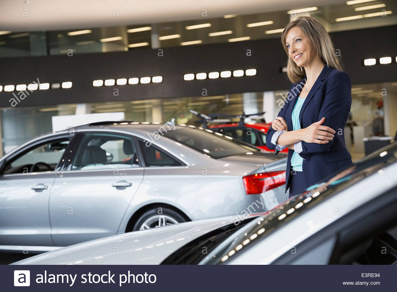 Confident saleswoman in car dealership showroom - Stock Image